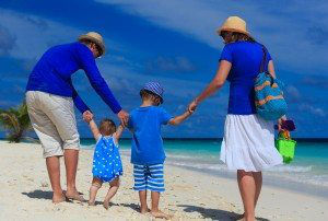 family with kids walking on tropical beach