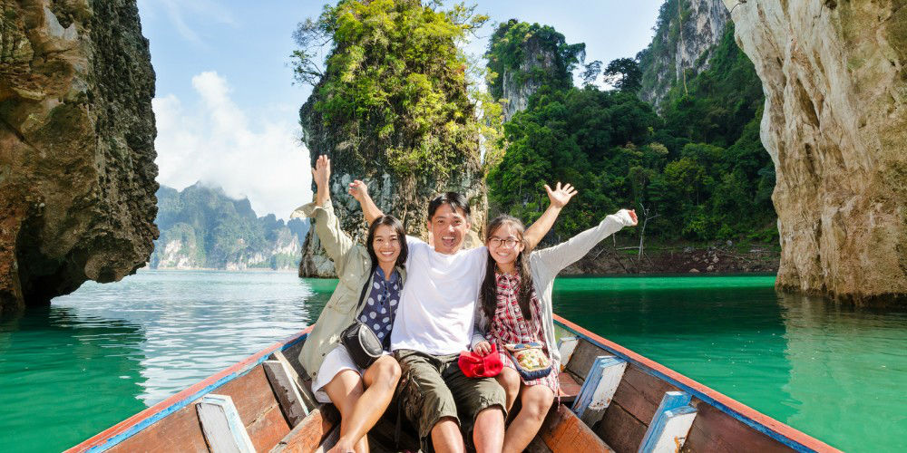 Happy family boat trip on summer vacation in Asia