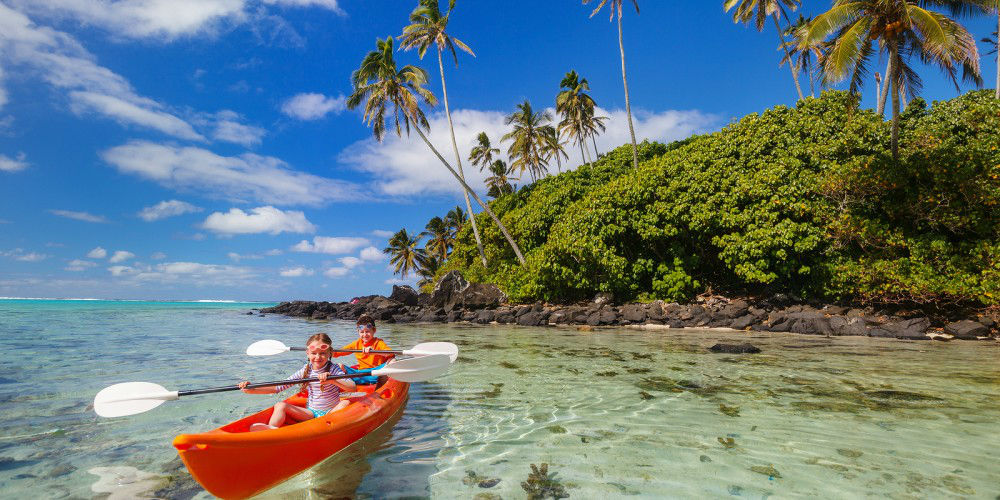 Kids enjoying paddling in colorful red kayak at tropical ocean w