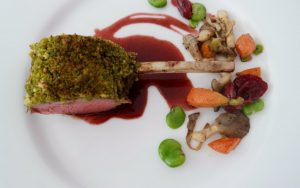 Pistachio and Herb Encrusted Rack of Lamb Cherry Madeira Jus.
