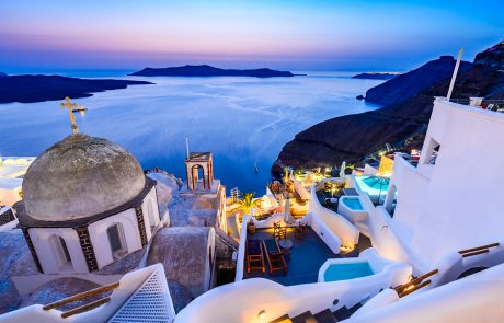 Fira Santorini - Greek Islands landmark with white village cobbled paths greek orthodox blue church and sunset over caldera. Cyclades Greece.