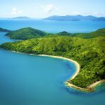 Aerial image of island in Whitsundays, Queensland Australia. Beautiful mountainous island with sandy white beach and turquoise water